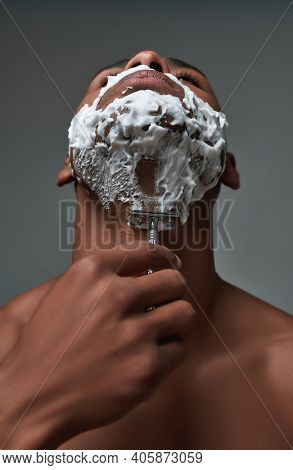 Close Up Of Young African American Man With Foam Applied On His Face Using Steel Razor For Removing
