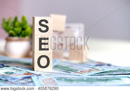Dollars Banknote With Calculator And Word Seo. Banknotes And Wooden Cubes With Letters Seo. Concept