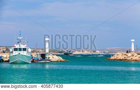 Ayia Napa, Cyprus - June 12, 2018: Agia Napa Marina, White Lighthouse Towers Stand At The Entrance B