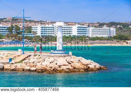 Ayia Napa, Cyprus - June 12, 2018: Agia Napa Marina View, White Lighthouse Tower Stands On A Breakwa