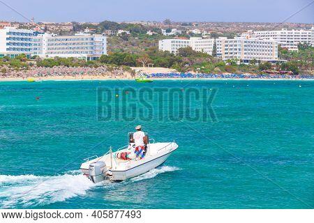 Ayia Napa, Cyprus - June 12, 2018:  White Pleasure Motor Boat With Driver Goes At Agia Napa Bay At S