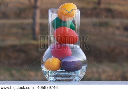 Colored Painted Easter Eggs In Glass Vase Or Carafe In Preparation For Holiday. Painting Chicken Or