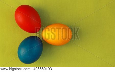 Round Red, Yellow And Blue Colored Easter Eggs On Vivid Green Background 2020 Concept. Painting Eggs