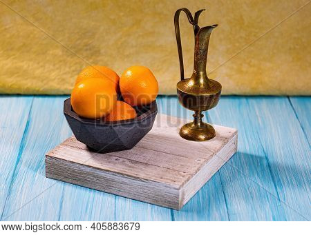 A Group Of Oranges In A Concrete Geodesic Bowl And A Etched Brass Urn On A Cyan Base With Light Yell