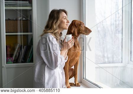 Happy Woman Owner And Her Vizsla Dog Sitting Together On Windowsill, Holding Cup Of Coffee, Looking