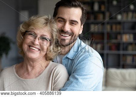Portrait Happy Young European Appearance Man Cuddling Elderly Retired Mother.