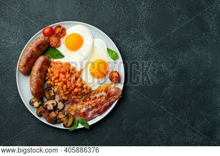 Full English Breakfast On A Plate With Fried Eggs, Sausages, Bacon, Beans, Toasts And Coffee On Dark