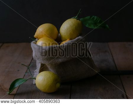 Lemons In A Hessian Sack. Fresh Picked Lemons Spilling From A Burlap Sack Onto A Rustic Wooden Surfa