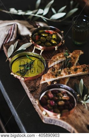 Pickled Greek Olives, Olive Oil And Herbed Focaccia Slices On Rustic Wooden Board, Selective Focus.