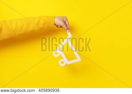 Shopping Cart In Hand Over Yellow Background