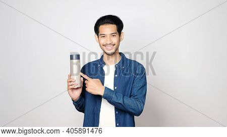 Sustainable And Zero Waste Concept, Young Asian Man Smiling And Holding Reusable Bottle Looking At C
