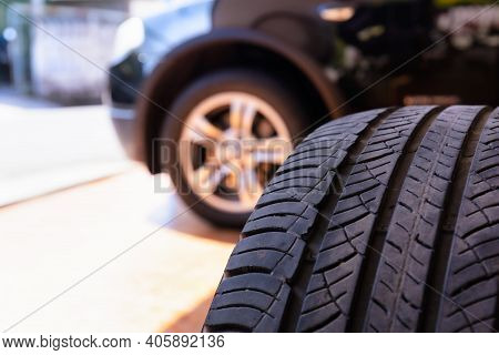 Close Up Of Old Tire With Car Wheel Background. Tire Workshop And Change Old Wheel On The Car. Used