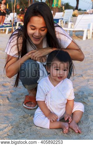 Happy Family Mother And Her Little Daughter Play At The Beach Together. Happy Little Girl Relax And