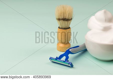 Ceramic Bowl With Lots Of Shaving Foam, Shaving Brush And Razor On A Blue Background. Set For Care O