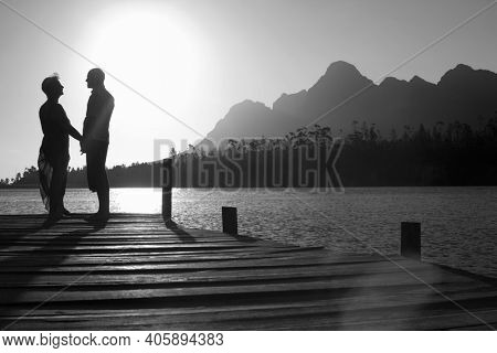 Black and white photo of senior couple showing affection in pier