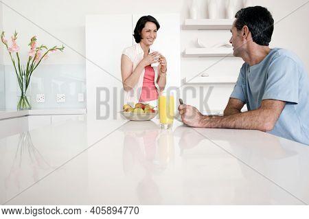 Happy couple having breakfast at kitchen bench