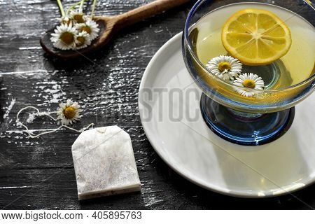 Chamomile Flowers And Chamomile Tea. Chamomile Tea In Cup With Flowers And Lemon, Close-up/ Deliciou