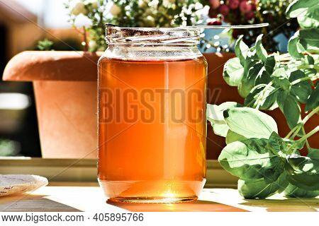 Organic Natural Honey In A Glass Jar / Bright Sunlight Shines Through A Jar Of Honey.