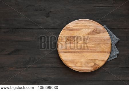 Empty Round Wooden Board On Black Wooden Kitchen Table, Top View, Copy Space. Wooden Platter, Copy S