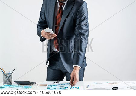 Businessman Standing Near Office Desk And Using Smartphone. Online Stock Trading And Investment. Cor