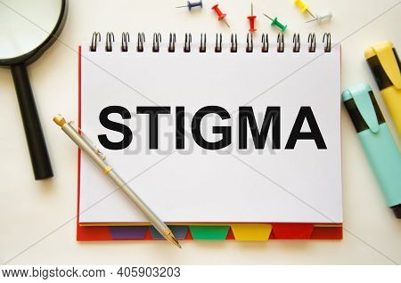 The Word Stigma Is Written On A Notebook And A White Background With A Half-glass Of Colored Pencils