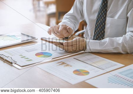 Business Man Or Analyst In A Modern Office Touching Smartphone While Reviewing Financial Statements