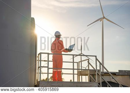 Man Engineer Working And Holding The Laptop For Check Performance Of Wind Turbine Farm Power Generat