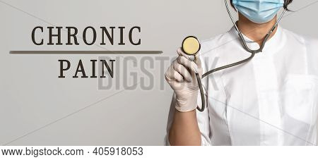 Chronic Pain - Concept Of Text On Gray Background. Nearby Is A Doctor In White Coat And Stethoscope.