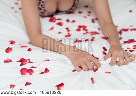 Woman Hand Grasping White Sheet And Rose Petals. Couple Making Love Or Having Sex In Bedroom.
