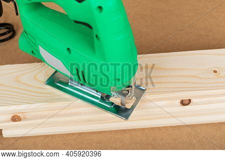 Picture Of A Green Jig Saw On A Wooden Background