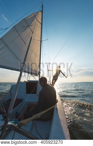 Romantic Couple In Love On Sail Boat At Sunset Under Sunlight On Yacht, A Man And A Woman Are Travel