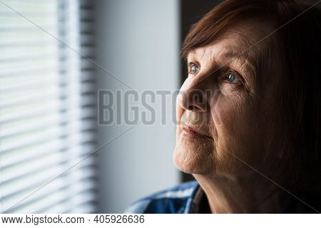 Portrait Of Lonely Senior Woman Who Is Looking Through Window.