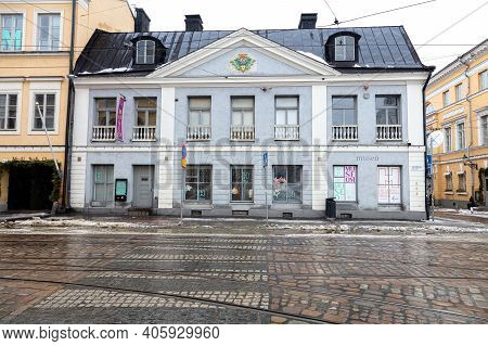 Finland, Helsinki. January 26, 2021 The Facade Of A Gray Building. The First Stone House In Helsinki