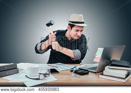 Angry And Frustrated Businessman Hold Hammer For Smash  Overworked At Desk Upset With Laptop Before