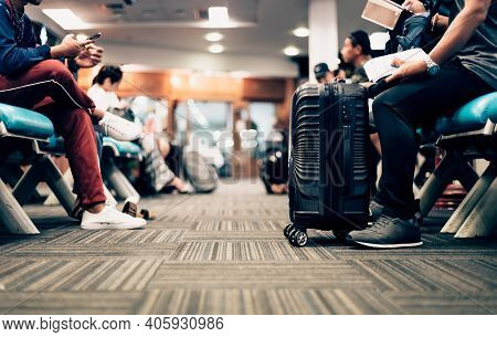 People Waiting For Check In At Airport. A Man And Luggage At The Airport Terminal.