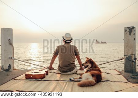 A Man Wear Straw Hat And Hug With A Dog Relax Near The Sea Sunset. Travel, Vocation, Holiday Concept