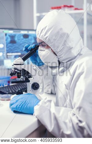 Researcher In Modern Microbiology Laboratory Uses Microscope Dressed In Ppe Suit. Virolog In Coveral