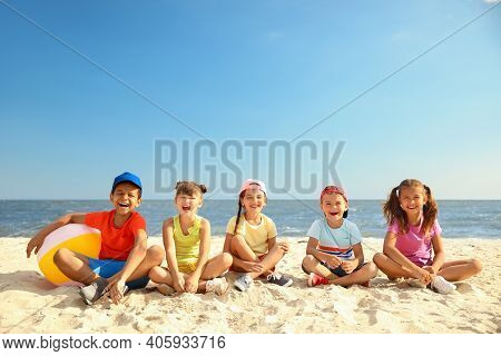 Group Of Happy Children Sitting On Sand At Sea Beach. Summer Camp