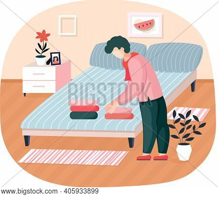 Young Man Householder Puts Bedclothes In Order At Home Standing Near Bed In Bedroom Neatly Stacks La