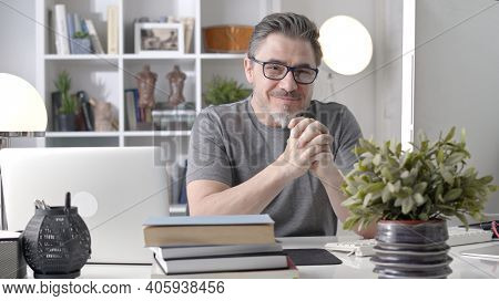 Portrait of happy older man in glasses sitting at desk working with laptop in home office. Confident 50s businessman in casual with gray hair smiling.