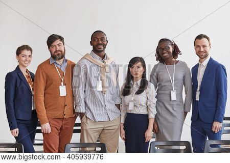 Multi-ethnic Group Of Business People Looking At Camera While Standing In Row Against White In Confe