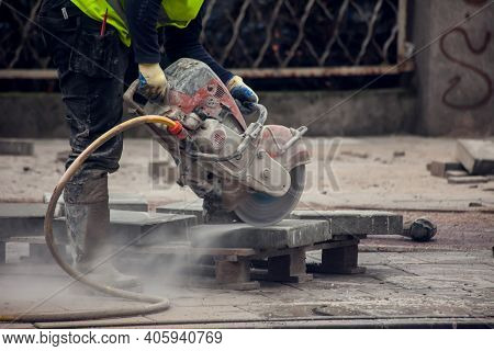 Cutting The Curb With With Cut-off Saw. Road Works
