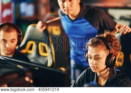 Three Young Focused Cybersport Gamers Looking At Pc Screen, Playing Online Video Games While Partici