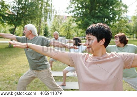 Mature woman exercising together with her group during sports training in the park outdoors