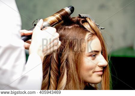Professional Hairdresser Makes Curls With A Curling Iron For A Young Woman With Long Red Hair In A B