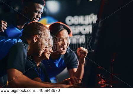 Team Of Excited Professional Cybersport Gamers Looking At Pc Screen And Celebrating Success While Pa