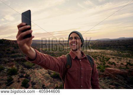 Portrait Of Happy Young Man Taking Selfie On Smartphone Against Morning Sunrise