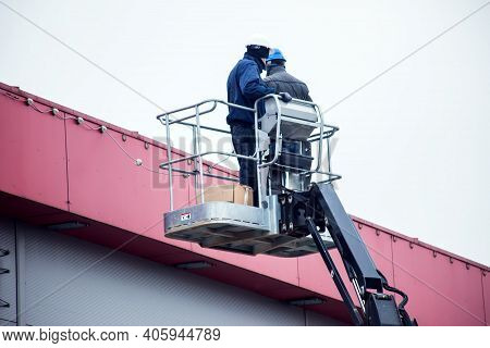 Professional Installation Work On A Construction Building Site. Assemblers Perform High-altitude Ins