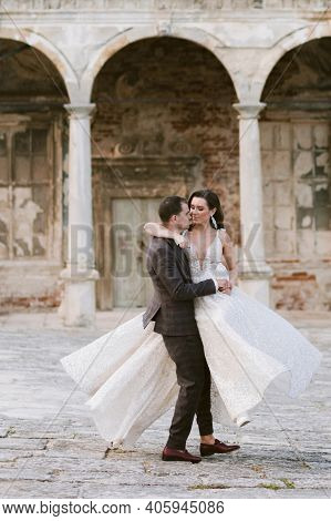 Groom Holding Bride In His Arms On The Background Of Ancient Building