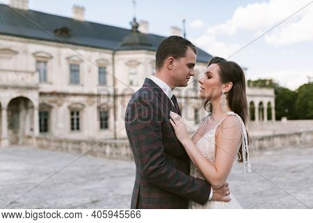 Bride And Groom Embracing And Looking At Each Other In The Background Of Palace